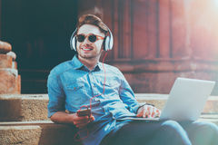 Cheerful handsome guy listening to music. Full og gladness. Joyful content smiling young man using laptop and listening to music while resting on the footsteps royalty free stock photos