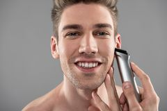 Cheerful handsome guy shaving with electric razor stock photo