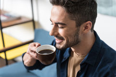 Cheerful handsome guy taking pleasure from hot drink Stock Images