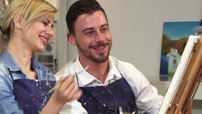 Cheerful handsome male artist and his girlfriend painting together at Art Studio. Close up of a bearded handsome male artist talking to his beautiful girlfriend royalty free stock image