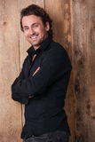 Cheerful handsome man in black shirt standing with arms crossed Stock Photo