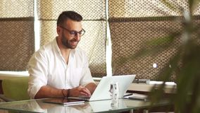 Cheerful handsome man businessman at work in the office. Smiling looks into the frame. The guy wears a white shirt stock video