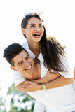 Cheerful handsome man carrying his girlfriend piggyback Royalty Free Stock Photo