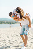 Cheerful handsome man carrying his girlfriend piggyback Royalty Free Stock Images