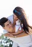 Cheerful handsome man carrying his girlfriend piggyback Royalty Free Stock Image