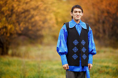 Cheerful, handsome man dressed in traditional national costume blue, black jacket decorated with ornaments. Blurred background. Stock Photo