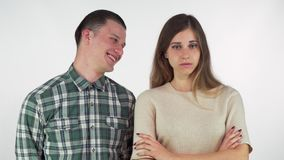Cheerful handsome man laughing at his annoyed girlfriend, isolated. Gorgeous young woman looking angry with her arms crossed, her boyfriend smiling at her stock video footage