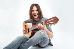 Cheerful handsome man with long hair sitting and playing guitar Royalty Free Stock Photo