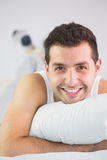 Cheerful handsome man lying in bed looking at camera. In bright bedroom Stock Image