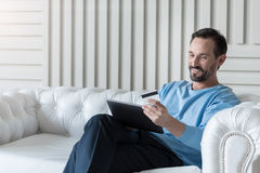 Cheerful handsome man making an electronic payment Stock Photography