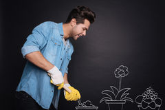 Cheerful handsome man planting flowers. Stock Photography