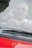 Cheerful handsome man in red convertible having phone call Royalty Free Stock Photos