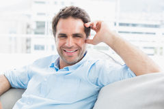 Cheerful handsome man relaxing on the couch looking at camera Royalty Free Stock Images
