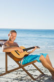 Cheerful handsome man strumming guitar Stock Photography