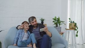 Cheerful handsome man is taking selfie with his cute little son using smartphone, they are posing, talking and gesturing. Self-portrait, technologies and happy stock video footage