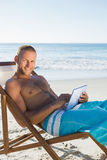 Cheerful handsome man using his tablet while sunbathing Stock Photo