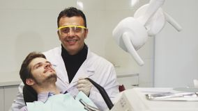 Professionl mature male dentist performing dental examination stock photos
