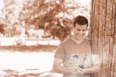 Cheerful handsome student using his digital phone Stock Photos