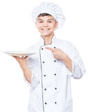 Teen boy wearing chef uniform. Cheerful handsome teen boy wearing chef uniform. Portrait of a happy cute male child cook with empty plate, isolated on white Royalty Free Stock Photography