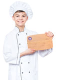 Teen boy wearing chef uniform. Cheerful handsome teen boy wearing chef uniform. Portrait of a happy cute male child cook with wooden chopping board for menu Stock Photography