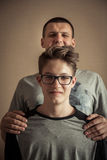 Cheerful handsome teenager boy with father as family portrait stock photo