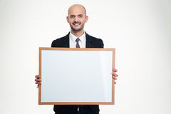 Cheerful handsome young businessman holding blank board Stock Image