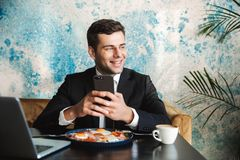 Cheerful handsome young businessman sitting in cafe using laptop computer have a breakfast or dinner eat using mobile phone stock image