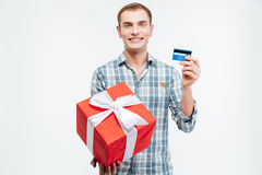 Cheerful handsome young man holding present and credit card Stock Photography