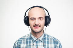 Cheerful handsome young man listening to music in headphones Stock Photos