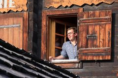 Good morning Switzerland. Cheerful handsome young man in the morning sunshine looks out of the hotel room window and takes a breath of fresh mountain air to Royalty Free Stock Photography