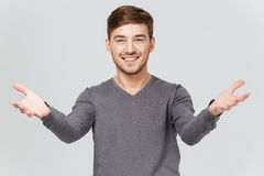 Cheerful handsome young man smiling and showing welcoming gesture Stock Photography