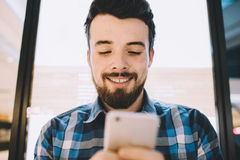 Cheerful handsome young man using his smartphone for chatting with friends. Inside of building. Always in touch. Smiling guy is happy to have this conversation stock photos
