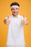 Cheerful handsome young sportsman showing thumbs up with both hands royalty free stock photos