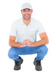 Cheerful handyman crouching on white background Stock Photo