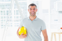 Cheerful handyman holding hardhat at construction site Stock Photo