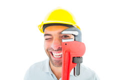 Cheerful handyman looking through monkey wrench Stock Photography