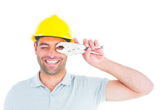 Cheerful handyman looking through pliers Royalty Free Stock Photos