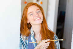 Cheerful happy attractive young woman painter with brush Royalty Free Stock Photography