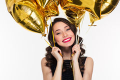 Cheerful happy beautiful woman in retro style holding golden balloons Royalty Free Stock Images