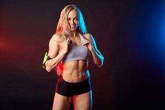 Cheerful happy blonde athlete showing her ideal slim body stock photography