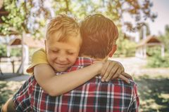 Cheerful and happy boy is hugging his father. Boy is keeping eyes closed and smiling. They are standing outside in park. Cheerful and happy boy is hugging his royalty free stock photography