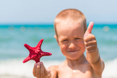 Cheerful and happy boy with starfish Stock Photos