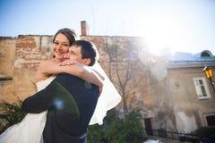 Cheerful happy bride  holds brunet groom Stock Image