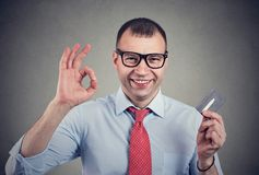 Cheerful happy business man with credit card showing Ok sign. On gray background royalty free stock photos