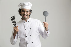 Cheerful happy chef holding kitchen utensil Stock Photos