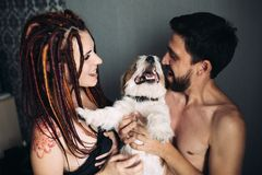 Cheerful and happy couple and the dog, smiling and showing tongu royalty free stock image