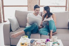Cheerful happy couple is doing online shopping in internet at ho. Me indoors. They are on cozy beige couch in casual clothes, relaxing and buying goods easily stock photo
