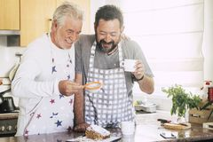 Cheerful and happy couple father son middle age and senior mature cooking cake together at home at the kitchen. using sugar and. Stuffs and have fun working royalty free stock photo