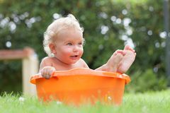 Cheerful happy cute curly baby is bathed in orange pelvis Stock Photos