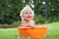 Cheerful happy cute curly baby is bathed in orange pelvis Stock Photo